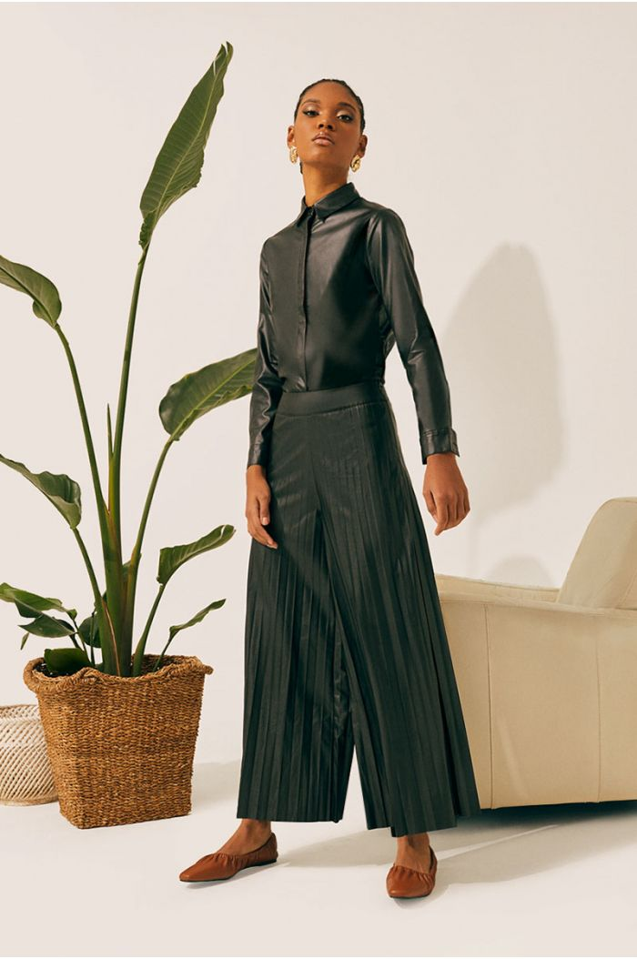 Model wears Wide cut pleated pants with leather look fabric