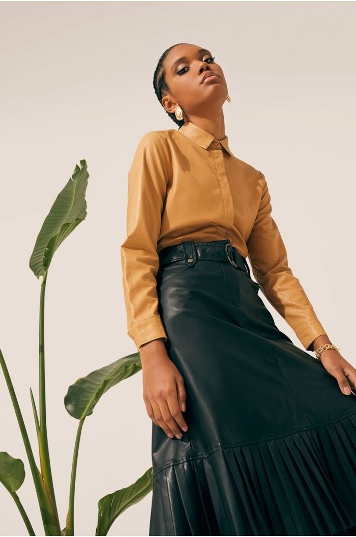 Model wears Knee high leather look skirt with pleated details